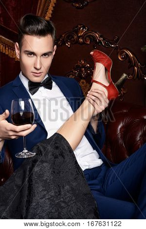 Fashion, shoes concept. Handsome man in evening suit holding female leg in fashionable shoes. Luxury.