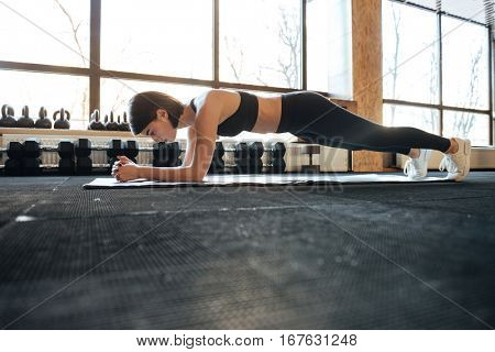 Concentrated young woman athlete training and doing plank exercise in gym