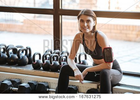Happy young woman athlete with earphones sitting and listening to music in gym