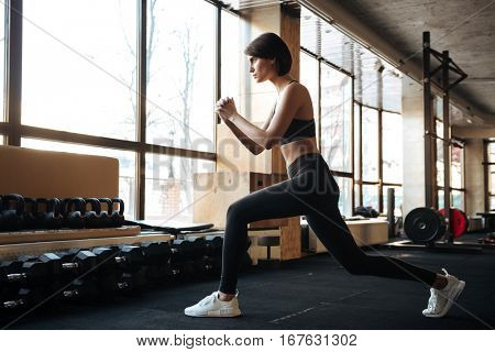 Serious young fitness woman working out and doing squats in gym