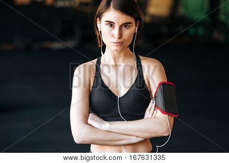 Confident young woman athlete with earphones standing with arms crossed in gym