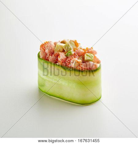 Japanese Sushi - Salmon and Avocado Gunkan Sushi with Tobiko on White Background. Cucumber Slice outside