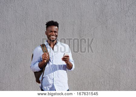 Attractive Man With Bag And Cellphone Standing By Wall