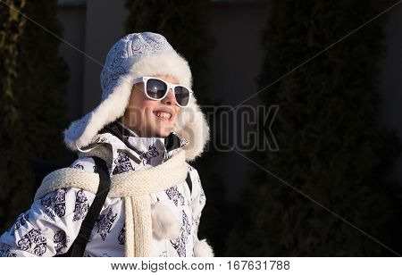 Portrait of a stylish little girl on the walking with winter clothes and sunglasses.Fashionable child. Caucasian stylish little girl in winter clothes walking outdoor