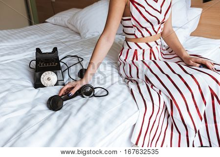 Closeup of woman with old retro telephone sitting on bed in the room