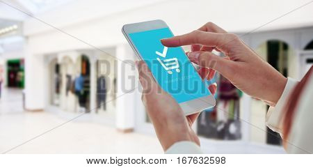 Cropped hand using smartphone against shopping mal
