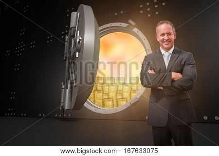 Smiling manager with arms crossed in warehouse against open grey safe
