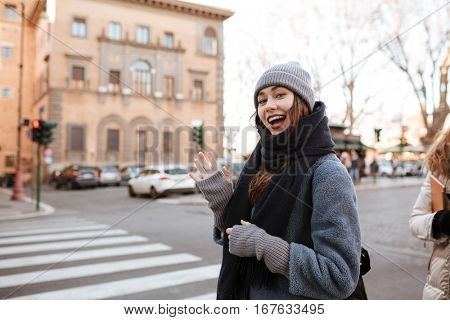 Happy beautiful young woman standing and showing hello gesture on the street of the city