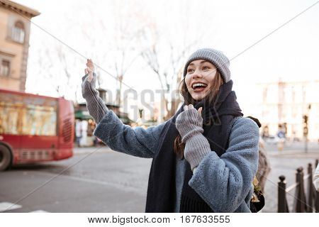 Happy pretty young woman trying to stop a taxi on the street of the city