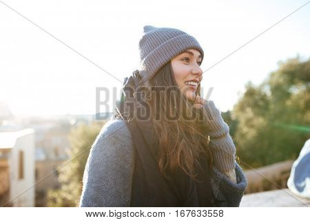 Cheerful pretty young woman walking outdoors in autumn