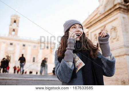 Happy amazed young woman talking on cell phone and pointing away in the city