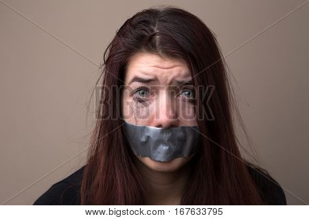 Frightened woman hostage with tape