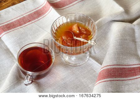Cup of tea and apple jam dessert or confiture on linen napkin