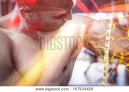Close-up of muscular man measuring biceps with tape measure in gym