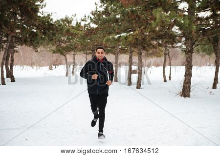 Active fitness man jogging on a snowy trail in winter forest