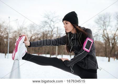 Close up portrait of a young fitness woman with armband stretching legs before running outdoors
