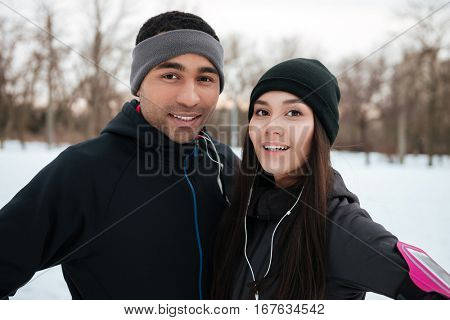 Portrait of a smiling happy multiracial fitness couple outdoors in winter