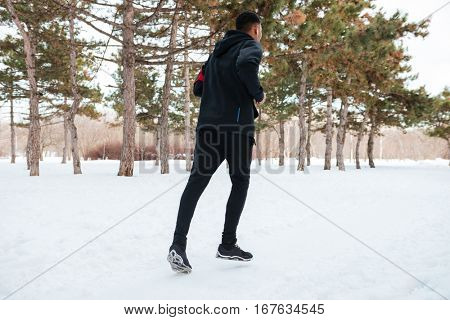 Back view of a young man running on snow covered winter road in forest