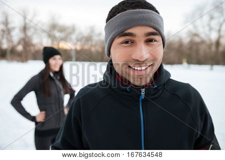 Close up portrait of a young afro american athlete looking at camera with his girlfriend on the background in winter forest