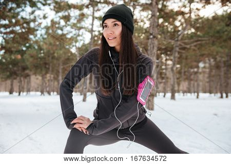Fitness woman doing stretching exercises before running outdoors in winter