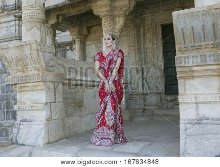 Beautiful Maharani. Young Indian Woman in Red bridal Sari clothing with bridal oriental jewelry. Beautiful Indian Girl in Wedding Sari. Indian Bride in the ancient Jain Temple Ranakpur. Wedding day