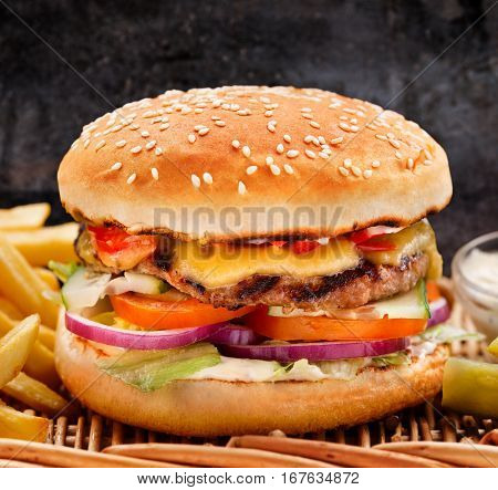 Delicious burger with fries on a wicker table