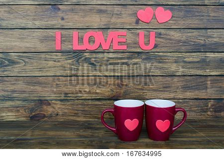 inscription I love you two flat pink hearts and two claret cup on a wooden background