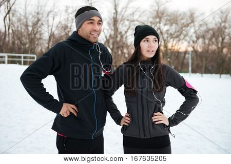 Smiling happy multiracial fitness couple having break after jogging outdoors in winter