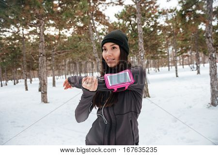 Cheerful young woman doing warming up before jogging outdoors in winter