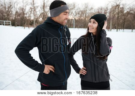 Smiling multiracial couple in sportswear laughing together outdoors in winter