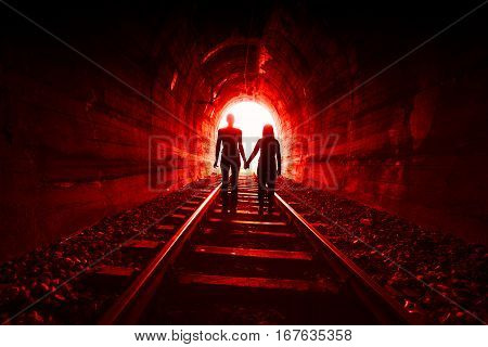 Couple walking hand in hand along the rails through a railway tunnel towards the bright at the end they appear as silhouettes against the light