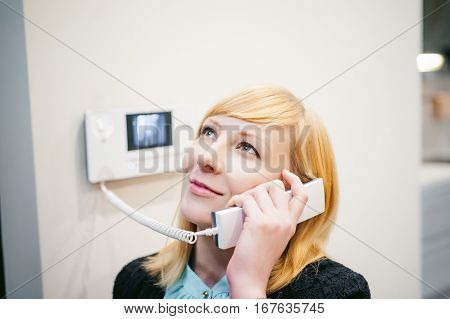 Smiling Blonde Woman Answers The Intercom Call, Hold The Phone To His Ear, Waiting For The Arrival O