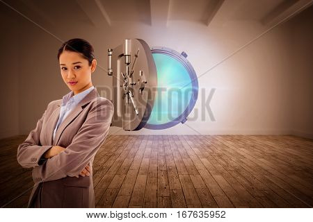 Portrait of a gorgeous businesswoman posing with the arms crossed against digital room