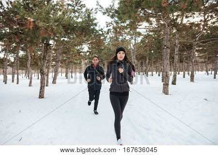 Runners jogging in snow in city park