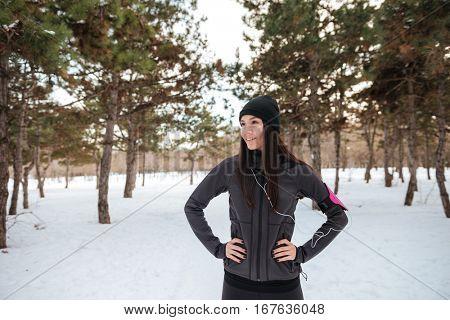 Young fitness woman in earphones having a break after jogging outdoors in winter