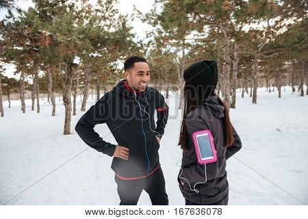 Athletic young couple talking while having break after jogging in winter forest