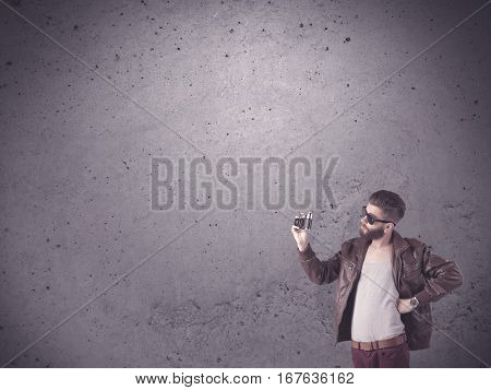 A stylish funny hipster person holding a vintage camera and taking photographs in front of a concrete clear empty urban wall background concept