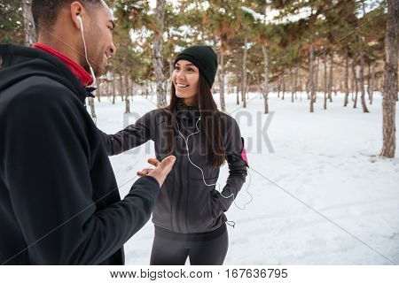 Smiling young couple talking while having break after jogging in winter forest