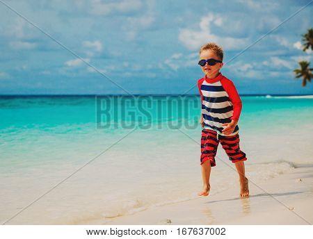 little boy run splashing water on tropical beach