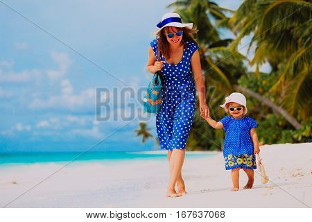 mother and cute little daughter walking on tropical beach