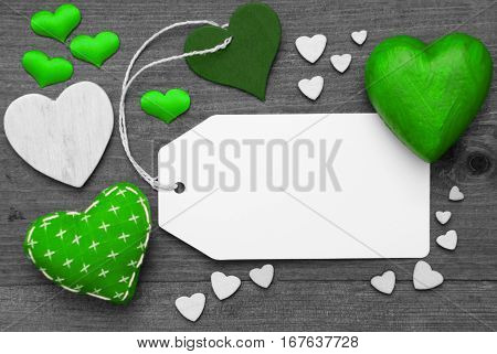 Label With Green Textile Hearts On Wooden Gray Background. Copy Space For Advertisement Or Your Free Text Here. Retro Or Vintage Style. Black And White Image With Colored Hot Spot.