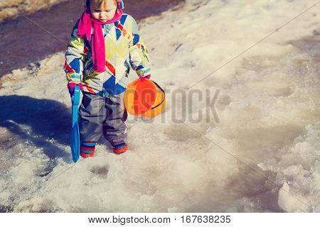 little girl playing in water puddle in spring snow