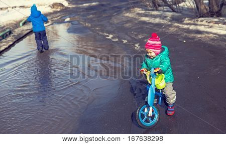 little girl riding bike and boy on scooter play in spring water puddle