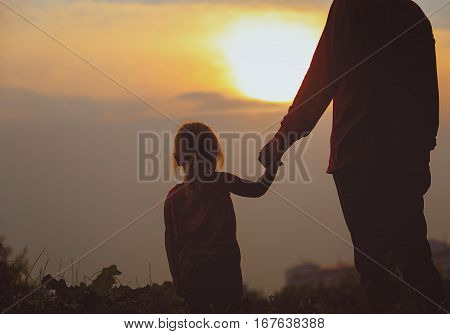 silhouette of father and daughter holding hands at sunset sky