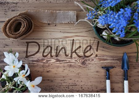 German Text Danke Means Thank You. Spring Flowers Like Grape Hyacinth And Crocus. Gardening Tools Like Rake And Shovel. Hemp Fabric Ribbon. Aged Wooden Background