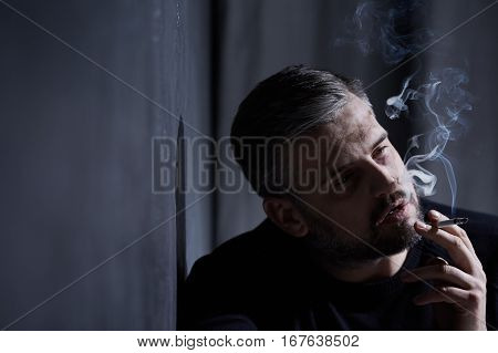 Alone man with depression inhaling cigarette smoke poster