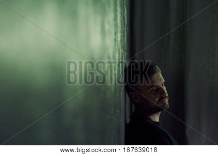 Lonely man sitting alone in gloomy room poster