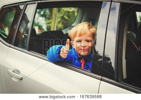 happy little boy loves to travel by car in nature