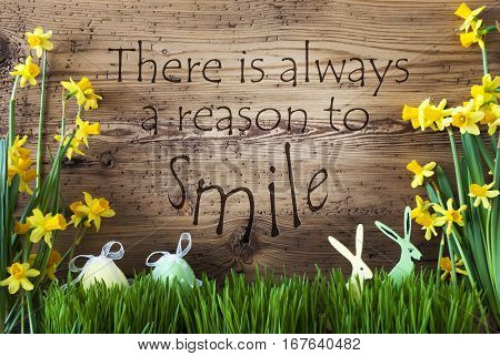 Wooden Background With English Quote There Is Always A Reason To Smile. Easter Decoration Like Easter Eggs And Easter Bunny. Yellow Spring Flower Narcisssus With Gras. Card For Seasons Greetings