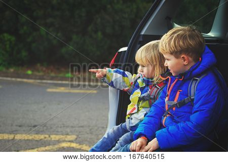 little boy and toddler girl travel by car, family tourism